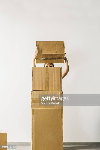 Girl stacking boxes against white background