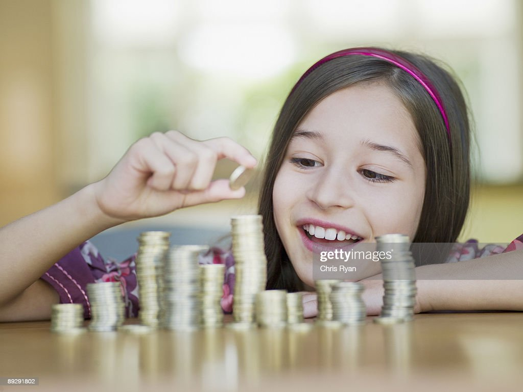 Girl stacking coins : Stock Photo
