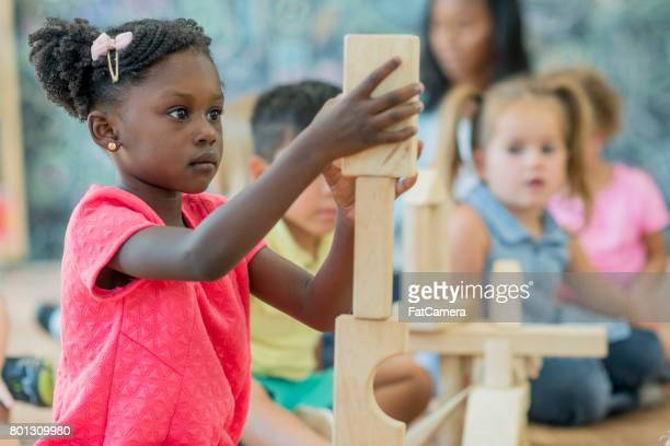 girl stacks blocks at preschool - non profit organization stock pictures, royalty-free photos & images