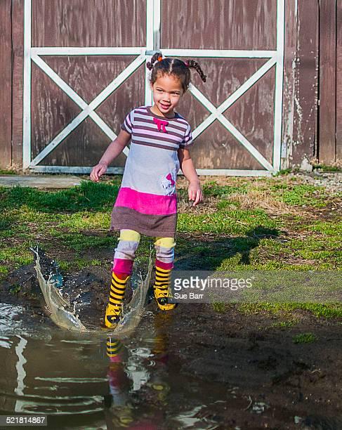 Girl stamping and splashing in garden puddle