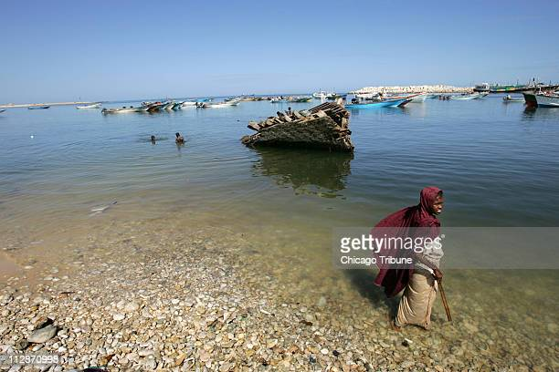 A girl stand on the beach in Bosaso Somalia October 13 2007 Bosaso is a hub for smuggling migrants Money brought in by pirates has contributed to...