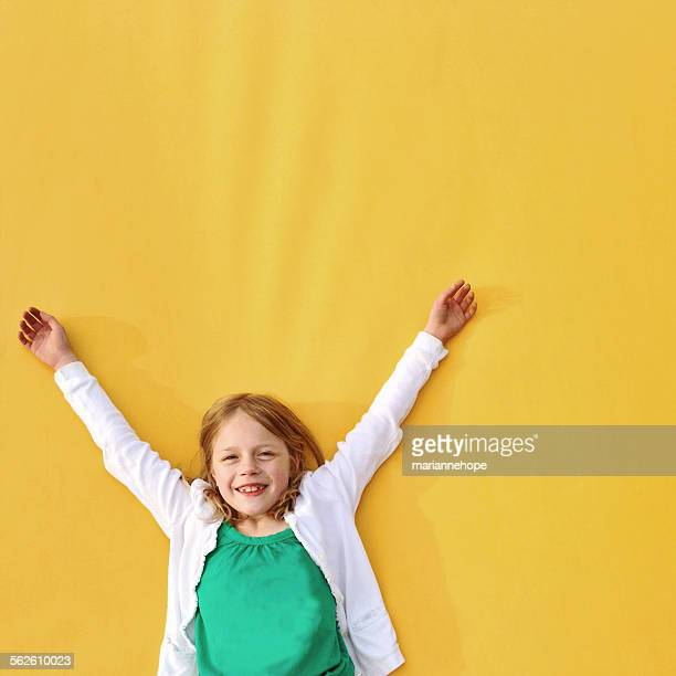 Girl standing against a yellow wall with her arms in the air
