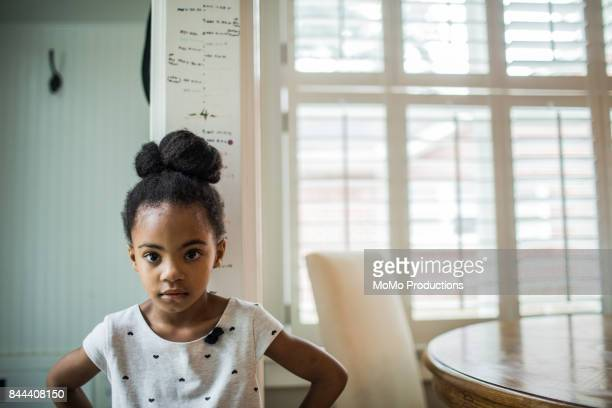 Girl standing against height chart on wall