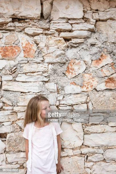 Girl Standing Against Stone Wall
