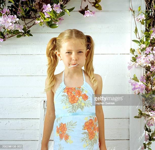 Girl (5-7) standing against white wall, eating lollipop