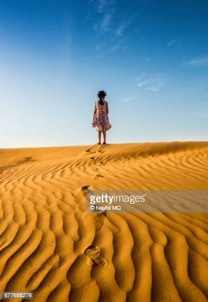 Girl standing alone on top of the dunes