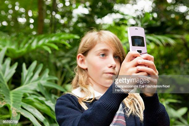 """girl standing amongst plants looking at cell phone - """"compassionate eye"""" stock pictures, royalty-free photos & images"""