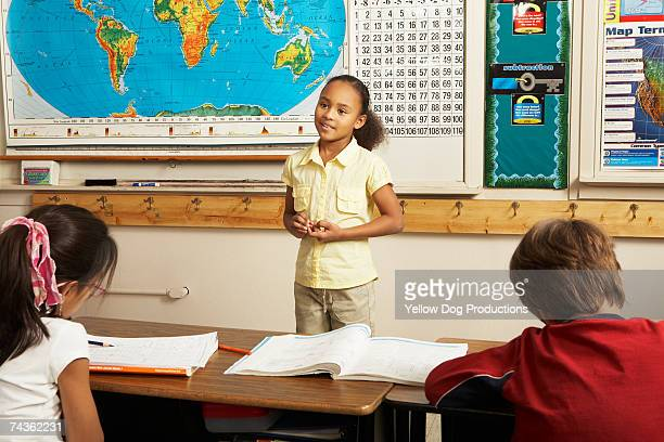 Girl (8-9) standing and talking in front of classroom to other children (8-11)