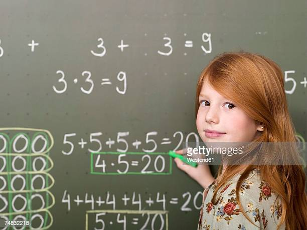 Girl (6-7) standing and writing on blackboard, portrait, close-up