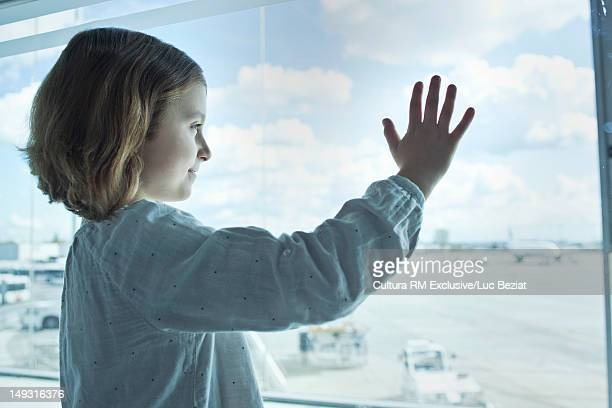 Girl standing at airport window