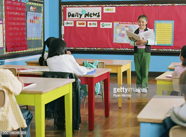 Girl (7-9) standing at front of classroom, giving presentation
