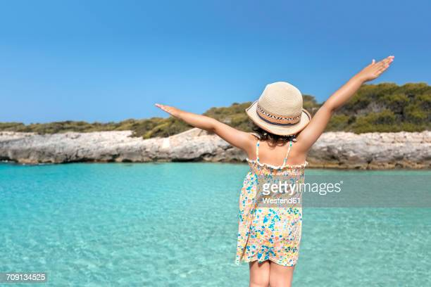 Girl standing at the beach with arms outstretched, rear view