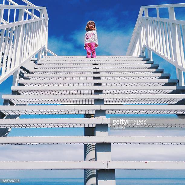 Girl standing at the top of a staircase