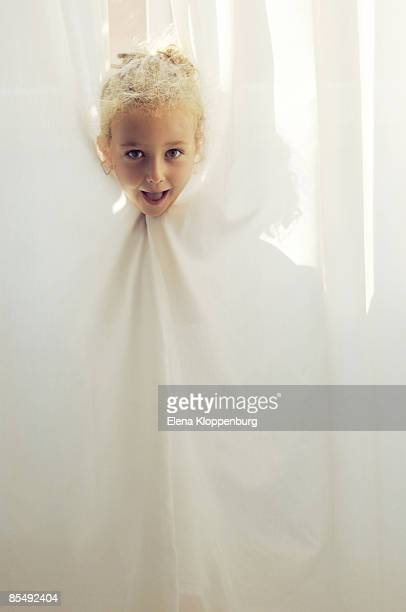 Girl standing behind curtain, portrait