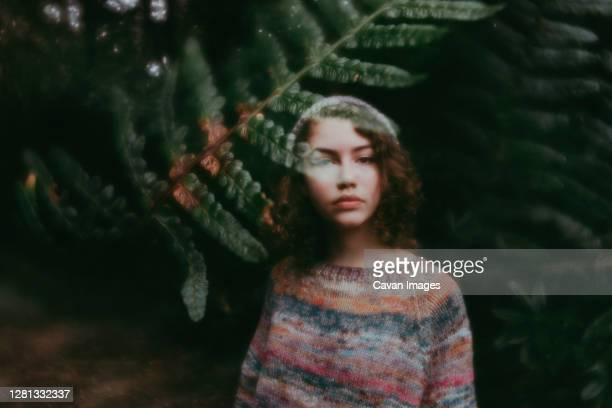 girl standing behind leaves in sweater and hat - digital composite stock-fotos und bilder