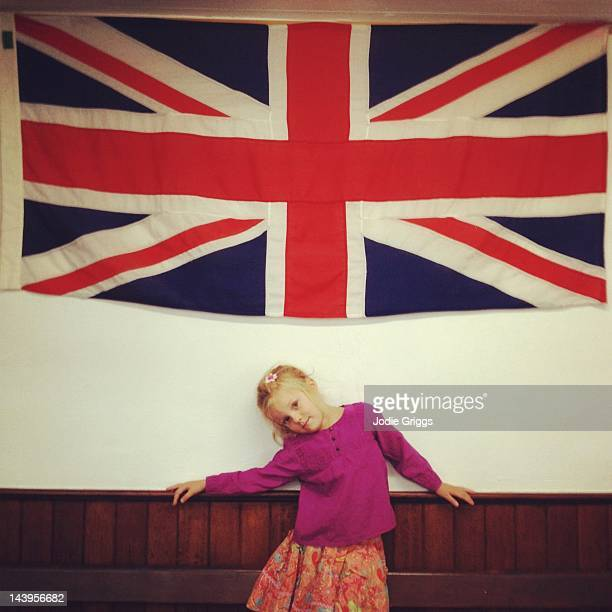 Girl standing beneath English flag