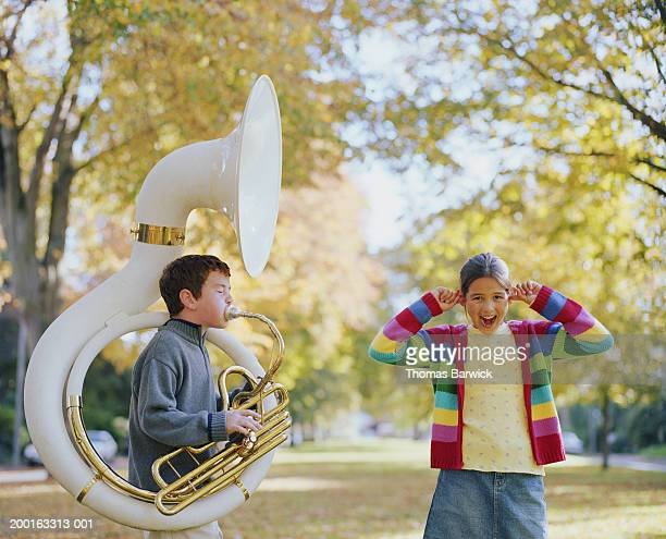 girl (8-10) standing beside boy (8-10) playing tuba, plugging ears - fingers in ears stock pictures, royalty-free photos & images