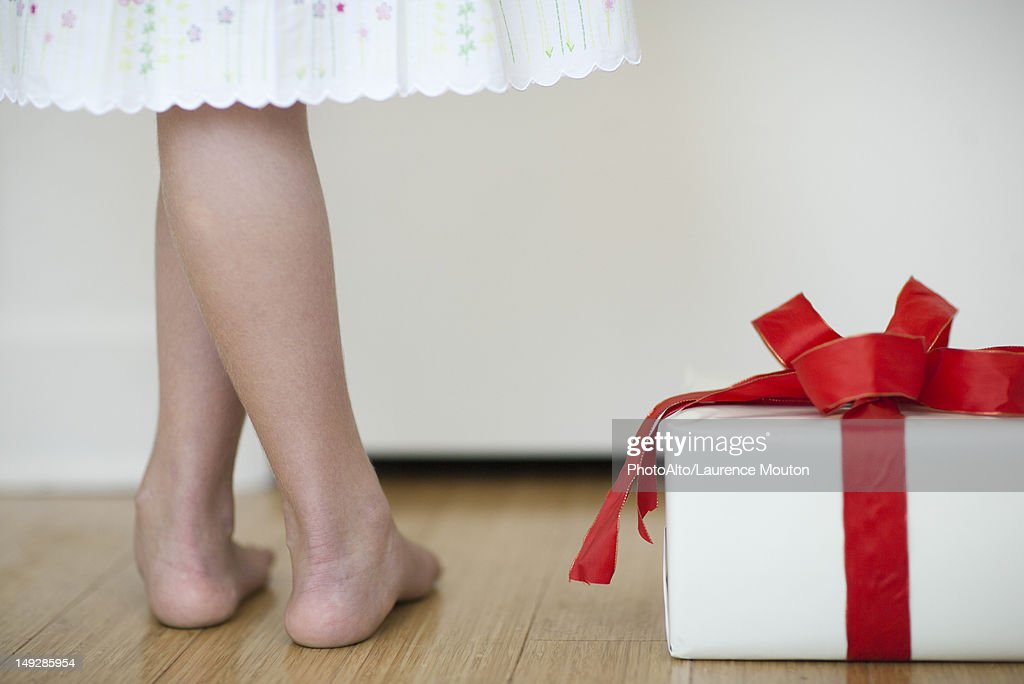 Girl standing beside wrapped gift, low section : Stock Photo
