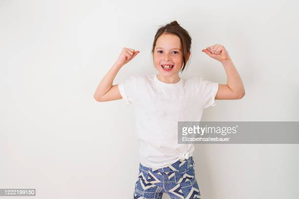 girl standing by a wall flexing her muscles - flexing muscles stock pictures, royalty-free photos & images