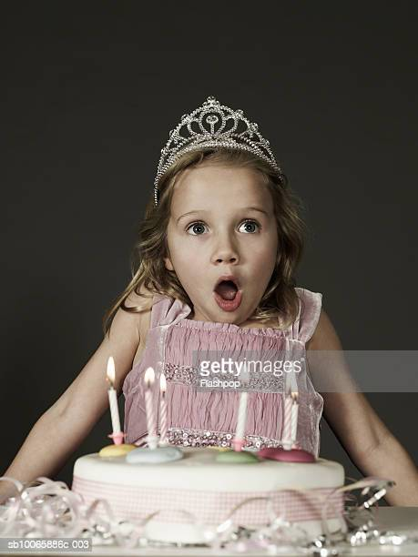 girl (6-7) standing by birthday cake, mouth open - happybirthdaycrown stock pictures, royalty-free photos & images