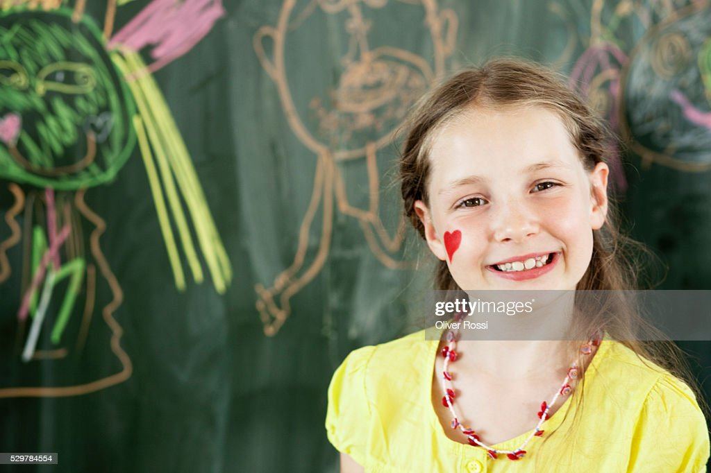 Girl standing by blackboard : Stock Photo