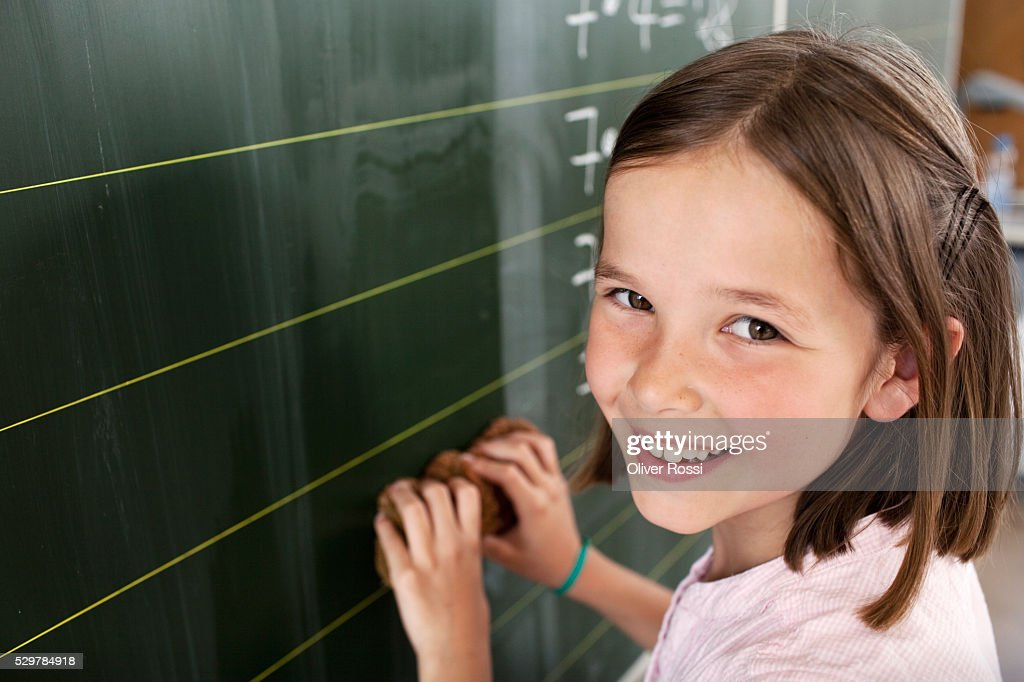 Girl standing by blackboard : Bildbanksbilder