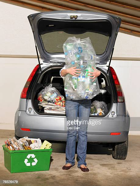 Girl (11-13) standing by car holding recycling