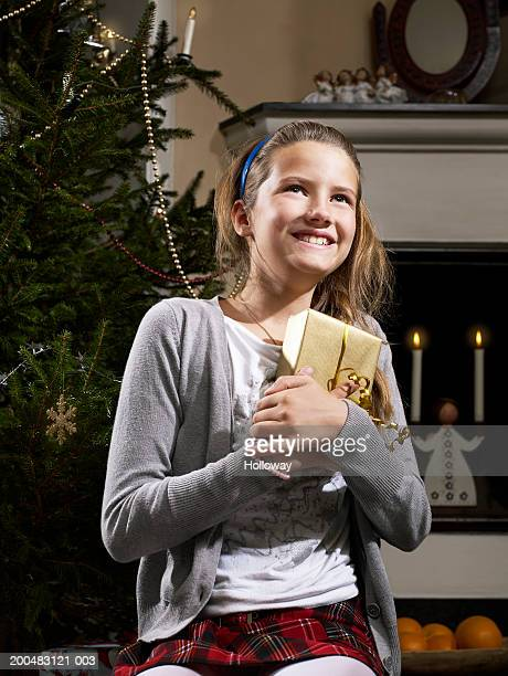 girl (9-11) standing by christmas tree holding present, smiling - girls in plaid skirts stock photos and pictures