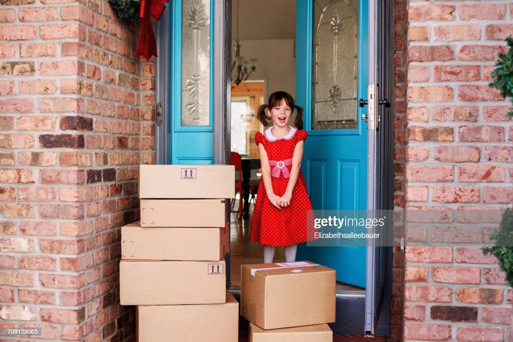 Girl standing by front door with delivery of boxes  Stock Photo & Girl Standing By Front Door With Delivery Of Boxes Stock Photo ...