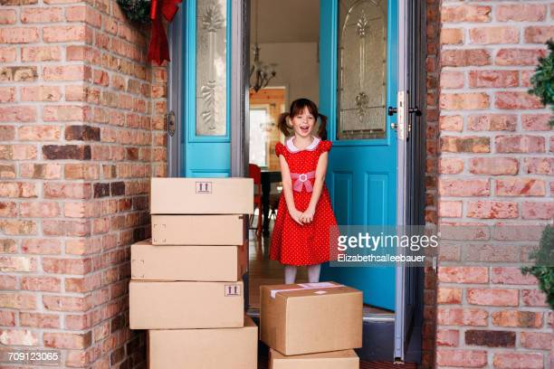 Girl standing by front door with delivery of boxes