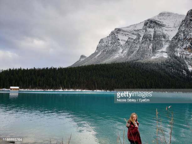 girl standing by lake against sky - sibley stock photos and pictures