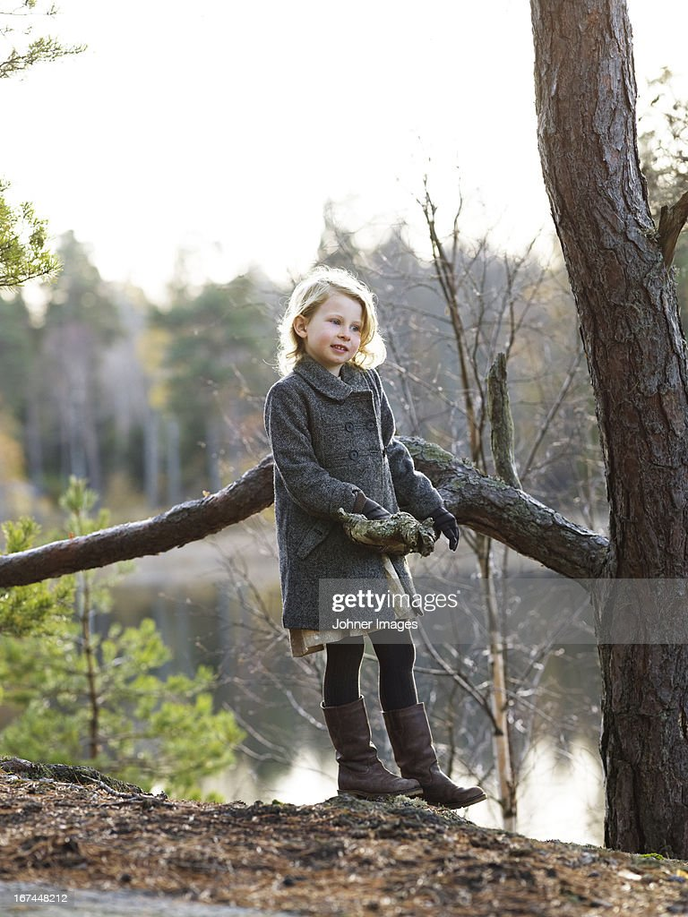 Girl standing by pine tree : Stock Photo