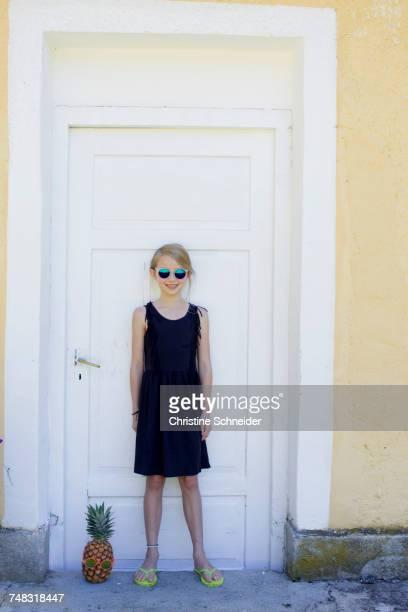 Girl standing by pineapple in front of door