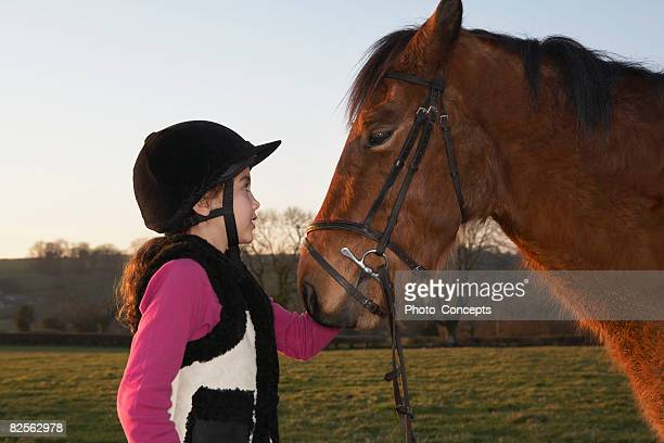 Girl standing by pony