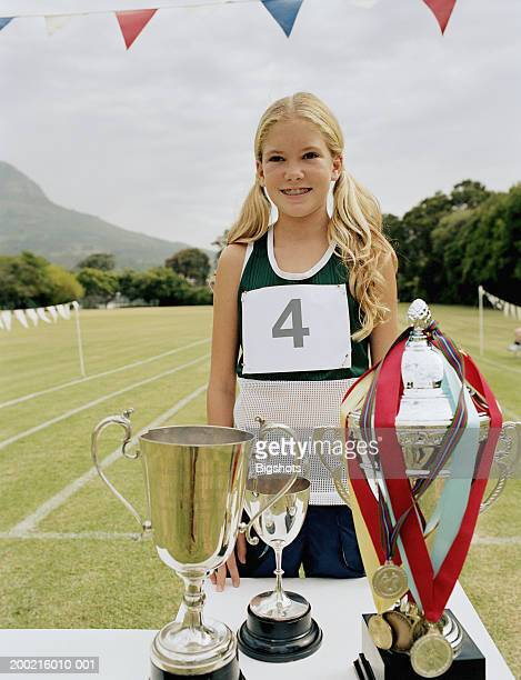 girl (10-12) standing by trophies at school sports day, smiling - 10 11 years stock photos and pictures