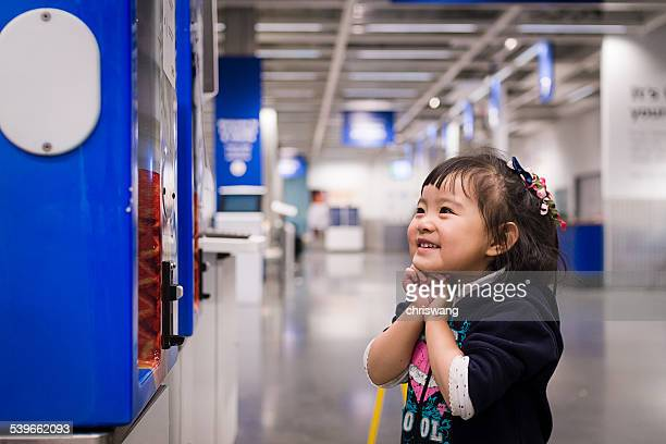 Girl standing by vending machine in corridor and smiling