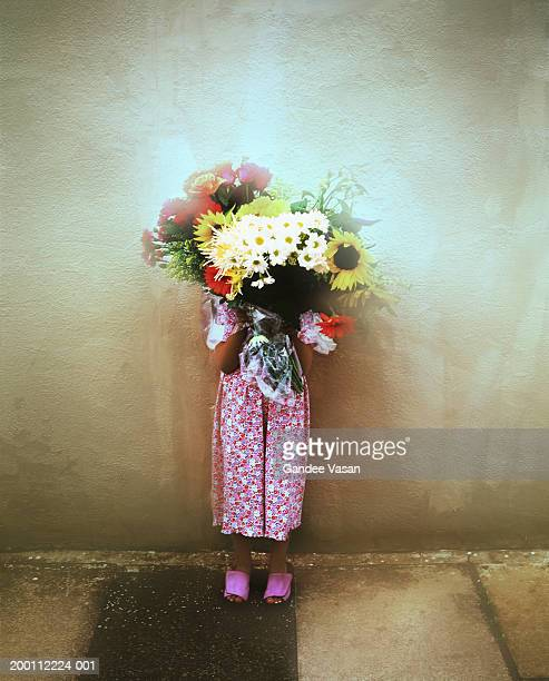 Girl (8-10) standing by wall holding bunch of flowers in front of face