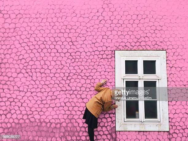 Girl Standing By Window Against Pink Wall