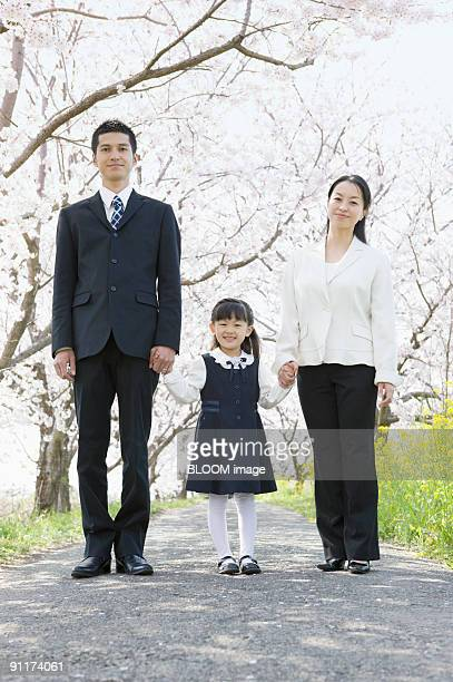 Girl standing hand in hand with parents under cherry blossom trees, portrait