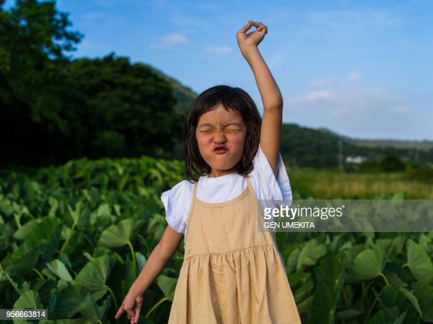 a girl standing in a field - 朗らか ストックフォトと画像