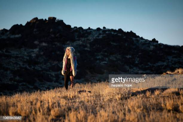 Girl standing in a field with volcanic rock.