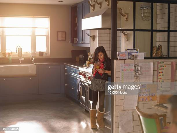 Girl standing in a sunny kitchen looking at phone