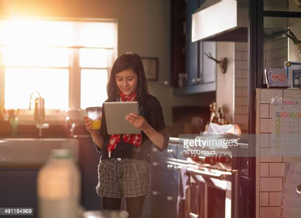 A girl standing in a sunny kitchen looking iPad