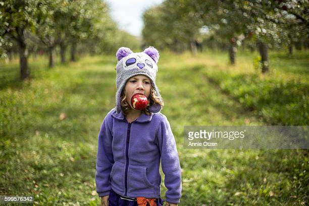 Girl Standing in an Apple Orchard with an Apple in her Mouth