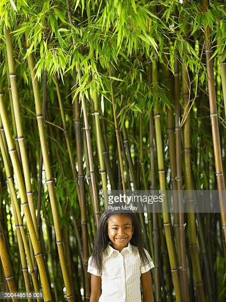 girl (5-7) standing in black bamboo grove, smiling, portrait - black bamboo stock pictures, royalty-free photos & images