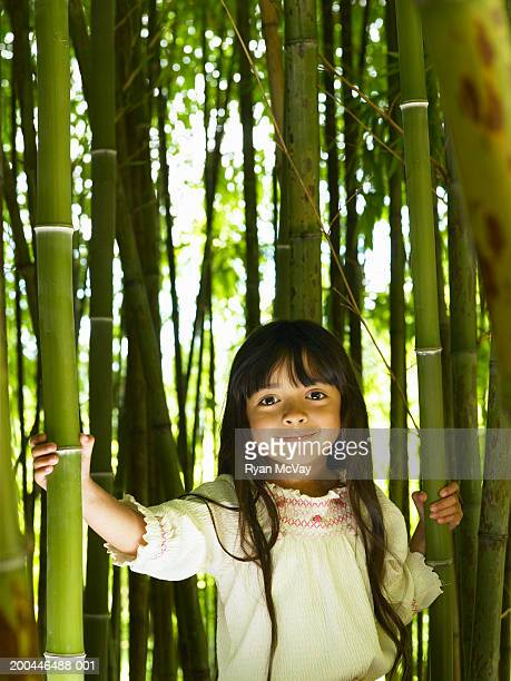 girl (4-6) standing in bory bamboo grove, smiling, portrait - black bamboo stock pictures, royalty-free photos & images