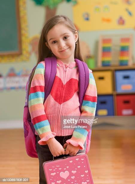 Girl (4-5) standing in classroom, smiling, portrait