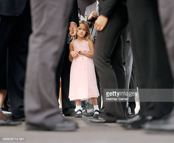 Girl (4-6) standing in crowd of businesspeople