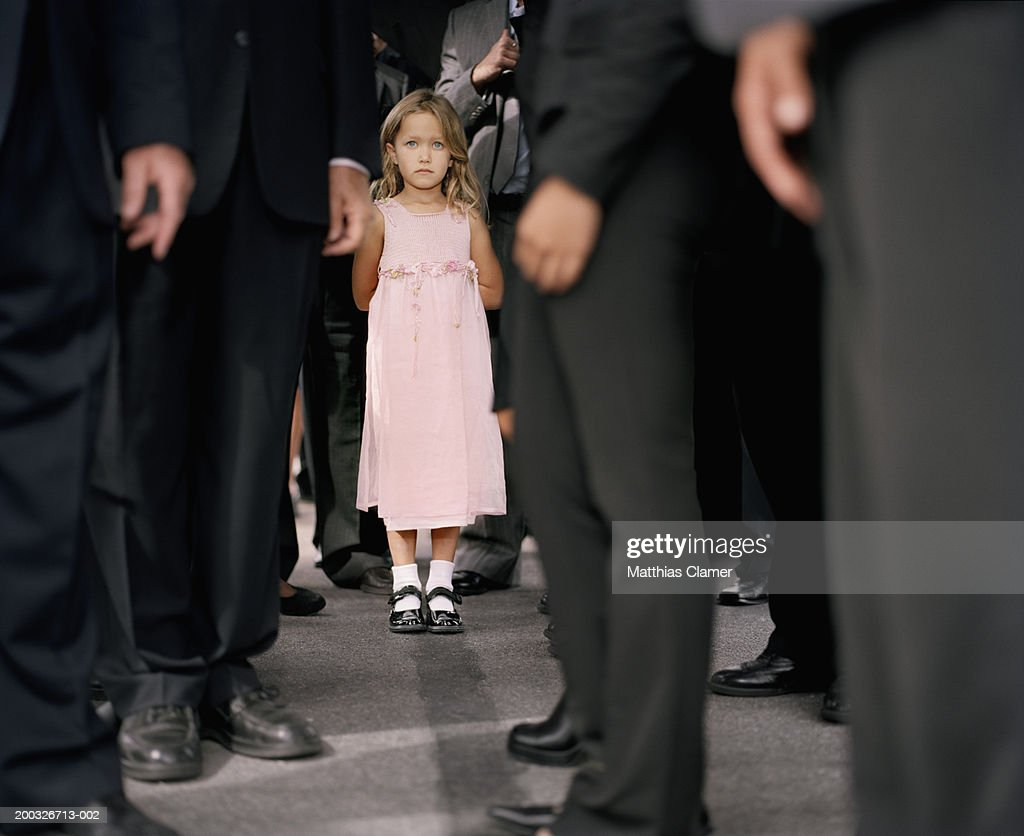 Girl (4-6) standing in crowd of businesspeople (focus on girl) : Stockfoto