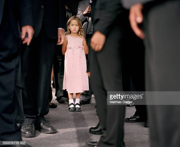 Girl (4-6) standing in crowd of businesspeople (focus on girl)